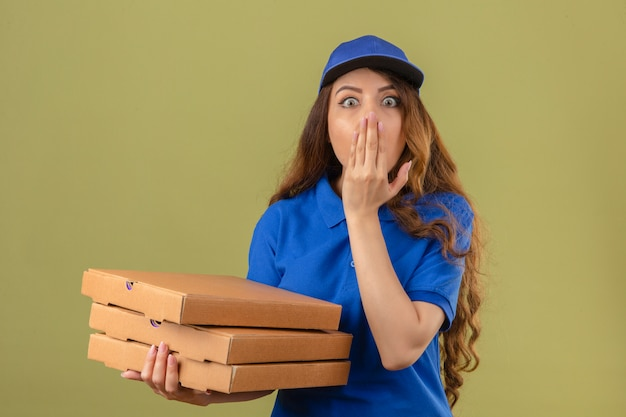 Young delivery woman with curly hair wearing blue polo shirt and cap with stack of pizza boxes shocked covering mouth with hand standing with wide opened eyes over isolated green background