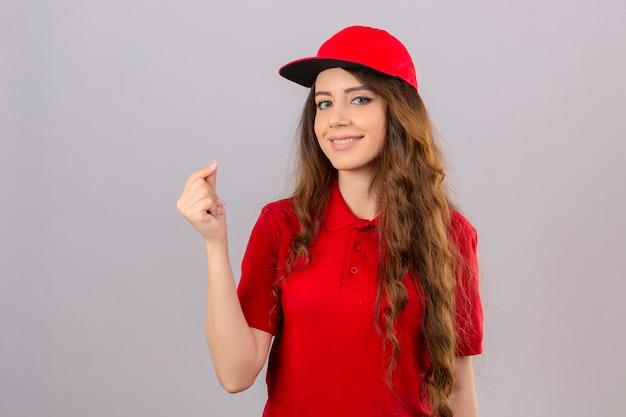 Молодая курьерская женщина с вьющимися волосами в красной рубашке поло и кепке делает денежный жест, дружелюбно улыбаясь на белом фоне
