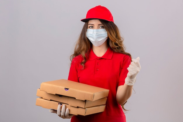 Young delivery woman with curly hair wearing red polo shirt and cap in medical protective mask and gloves standing with pizza boxes doing a money gesture smiling over isolated white background