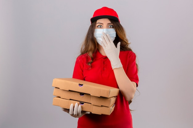 Young delivery woman with curly hair wearing red polo shirt and cap in medical protective mask and gloves standing with pizza boxes looking surprised covering mouth with hand over isolated white ba