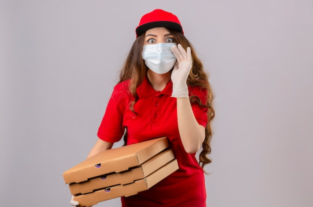Giovane donna delle consegne con i capelli ricci che indossa polo rossa e berretto in maschera protettiva medica e guanti in piedi con scatole per pizza che sembrano sorpresi con una mano vicino alla bocca che racconta un segreto è