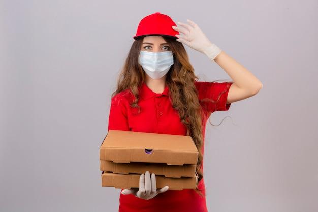 Giovane donna di consegna con i capelli ricci che indossa la maglietta polo rossa e il cappuccio in maschera protettiva medica e guanti in piedi con scatole per pizza salutando toccando il cappuccio cercando fiduciosi su backg bianco isolato