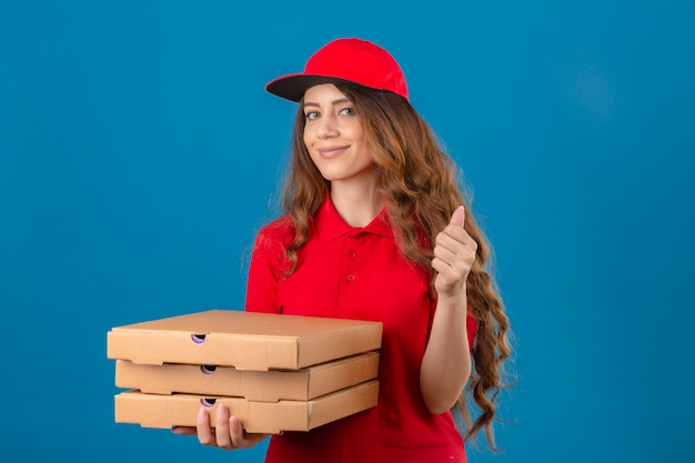 Young delivery woman with curly hair wearing red polo shirt and cap with stack of pizza boxes smiling showing thumb up over isolated blue background
