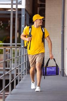 黄色い制服を着た若い配達員が、便利なスピードの快適さのアイデアをクライアントに届けます