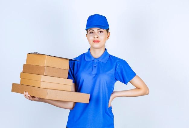 Giovane fattorina in uniforme blu che tiene scatole di cartone su sfondo bianco.