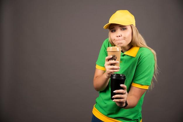 Молодая доставляющая покупки на дом, держа чашки кофе на черной стене.