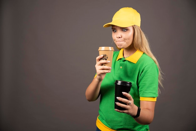 Молодая доставляющая покупки на дом, держа чашки кофе на темном фоне. фото высокого качества