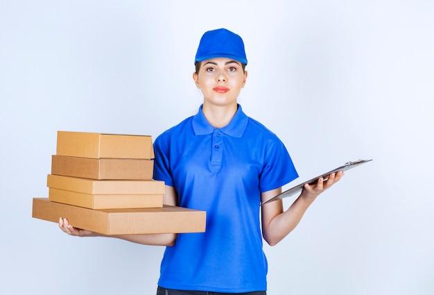 Молодая доставляющая покупки на дом в синей форме, держа картонные коробки и доску сзажимом для бумаги.