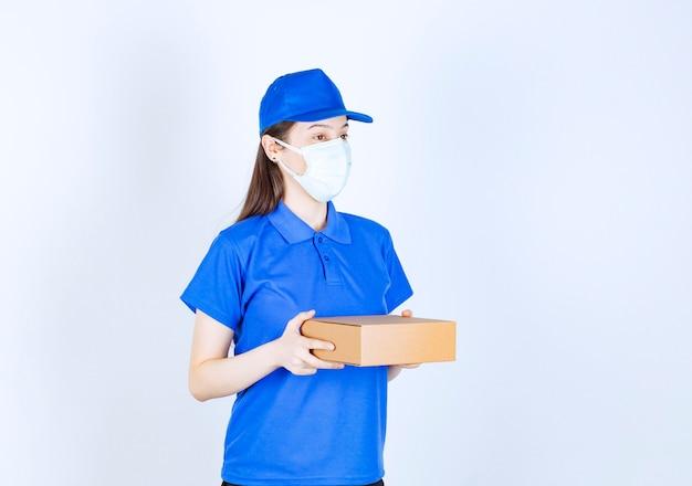 Giovane fattorina in maschera medica che tiene scatola di cartone su sfondo bianco.