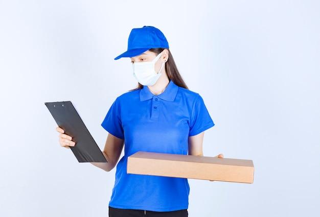 Giovane donna di consegna in maschera medica che tiene il pacchetto e controlla il nome del cliente.