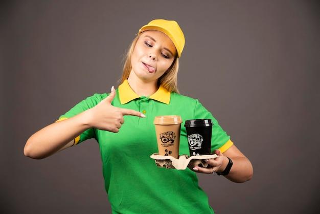 暗い背景にコーヒーのカップを指している若い配達員。高品質の写真