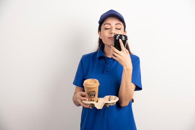Молодая доставщица нюхает одну чашку кофе
