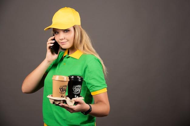 スマートフォンで話すコーヒーのカップを持つ若い配達員。