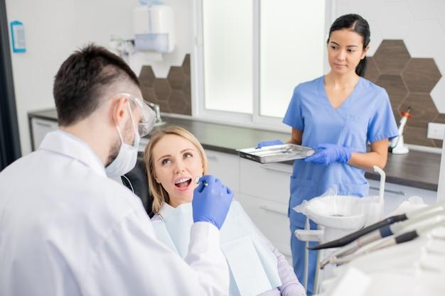 マスク、手袋、ホワイトコートを着た若い歯科医が、肘掛け椅子に座っている患者をかがめながら鏡で口頭検診を行う