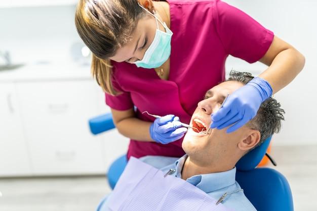 환자를 확인 하 고 젊은 치과 의사 여자.
