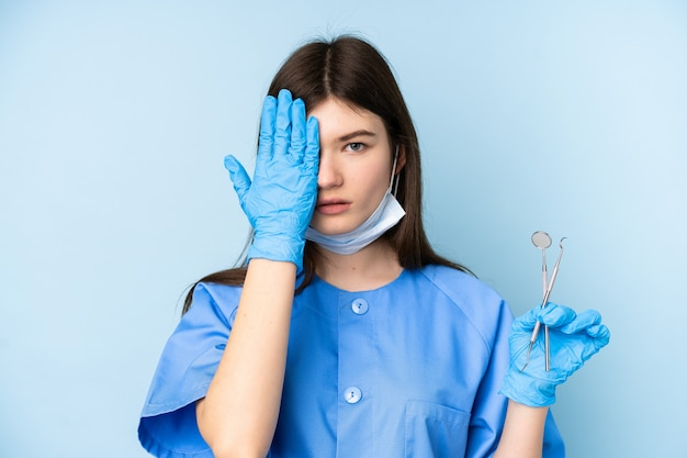 Young dentist woman holding tools over blue wall covering a eye by hand