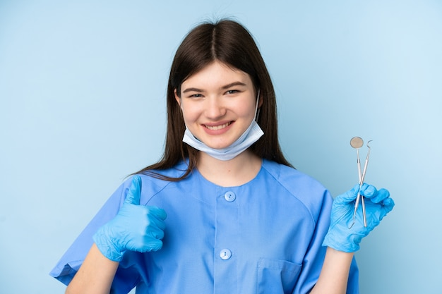 Young dentist woman holding tools giving a thumbs up gesture