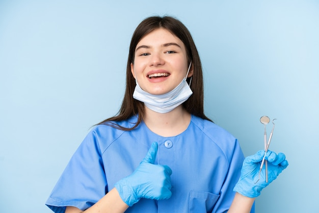 Young dentist woman holding tools over isolated blue wall giving a thumbs up gesture