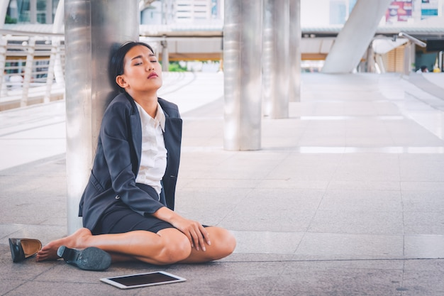 Young depressed businesswoman sitting on the floor