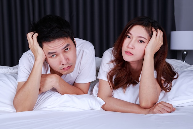 Young depressed couple on bed in bedroom