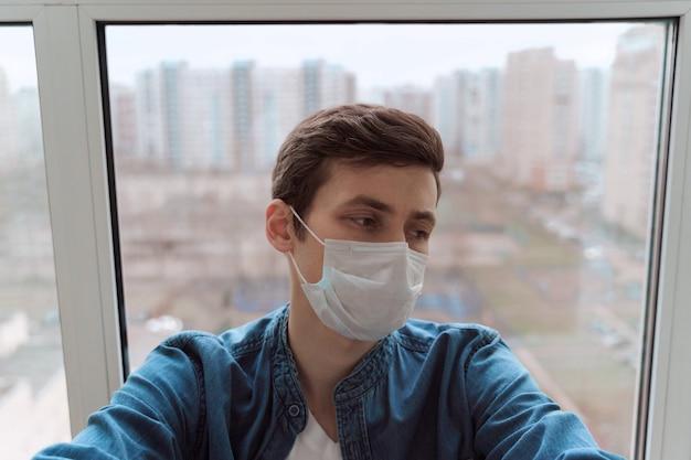 보호 얼굴 마스크를 착용하고 발코니에 앉아 우울한 젊은이
