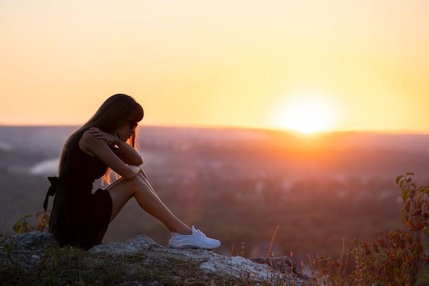 日没時に屋外で考えている山の丘の上に座っている黒い短い夏のドレスで若い落ち込んでいる女性。