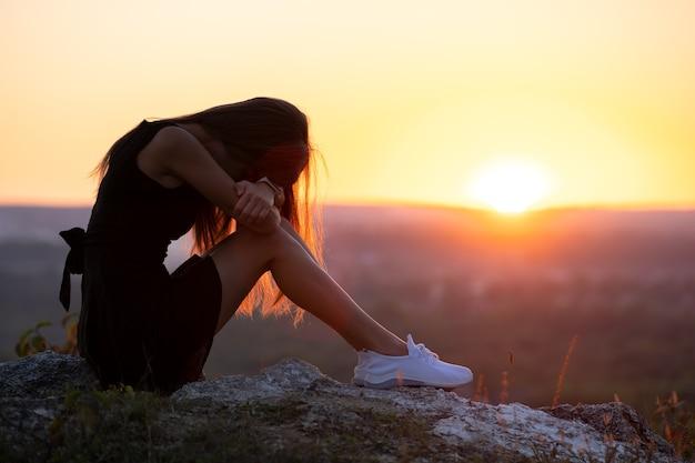 일몰에 야외에서 생각하는 바위에 앉아 검은 짧은 여름 드레스에 젊은 우울 된 여자. 자연 속에서 따뜻한 저녁에 고민하는 유행 여성.