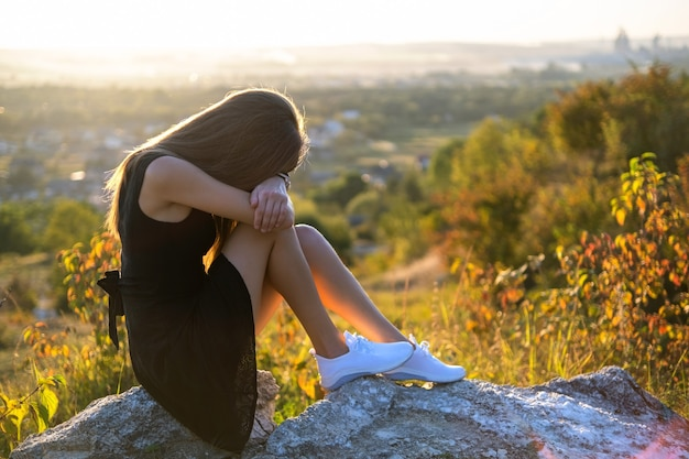 日没時に屋外で考えている岩の上に座っている黒い短い夏のドレスの若い落ち込んでいる女性。自然の中で暖かい夜を考えているファッショナブルな女性。
