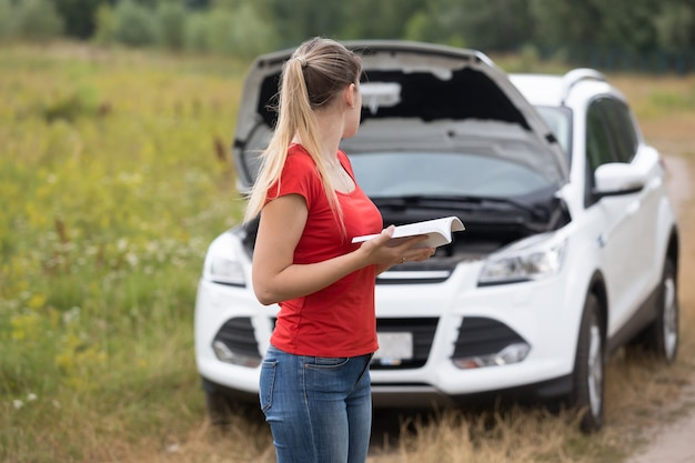 Young depressed woman looking at her broken car and reading owner manual