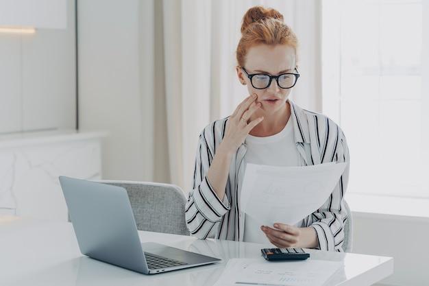 Молодая депрессивная женщина с финансовыми проблемами сидит за столом с ноутбуком и калькулятором