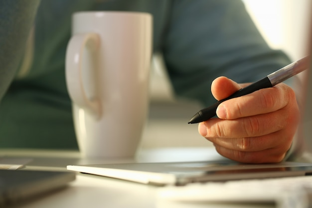 A young designer holds a pen from a tablet in his