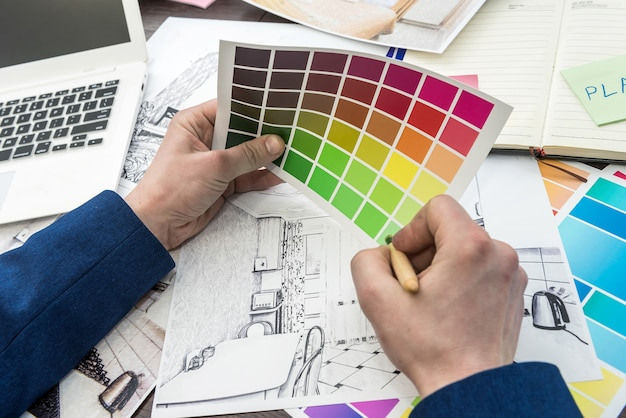 Young designer is working on a new project, choosing the perfect color for a modern apartment renovation