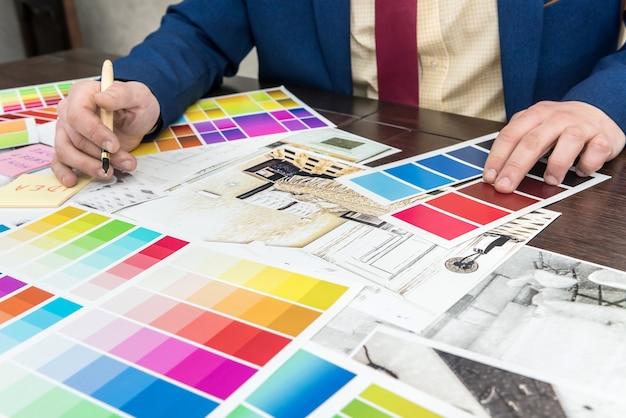 若いデザイナーが新しいプロジェクトに取り組んでおり、モダンなアパートのリフォームに最適な色を選択しています