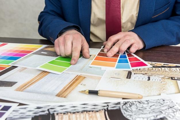 젊은 디자이너가 새로운 프로젝트를 진행하고 있으며 현대 아파트 리모델링을위한 완벽한 색상을 선택합니다.