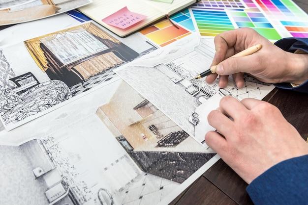 若いデザイナーは、色の選択とモダンなアパートの修理に取り組んでいます。オフィスの机の上にフラットで色付きのパターンをスケッチします