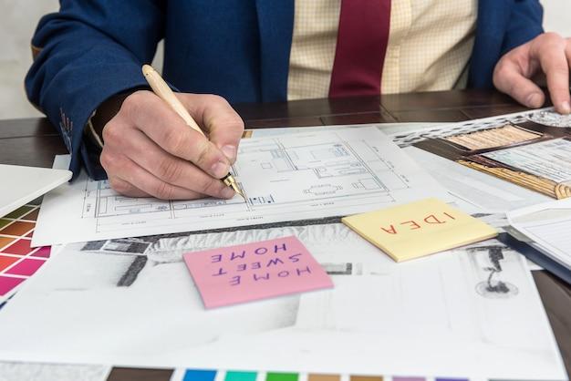 Молодой дизайнер работает над выбором цвета и ремонтом современной квартиры. нарисуйте плоские и цветные узоры на столе в офисе