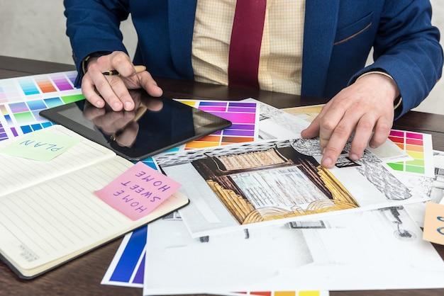 젊은 디자이너는 현대 아파트의 색상 선택 및 수리를 위해 노력하고 있습니다. 프리미엄 사진