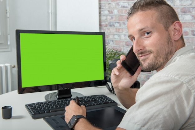 Young designer man uses a graphic tablet and phone, green screen