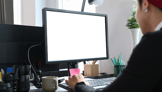 Young designer sitting at graphic studio in front of computer