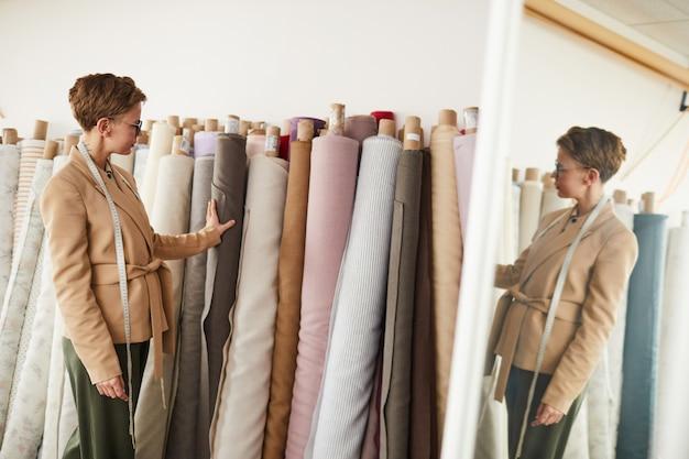 Молодой дизайнер стоит возле рулонов с текстилем и выбирает ткань для будущей одежды в мастерской