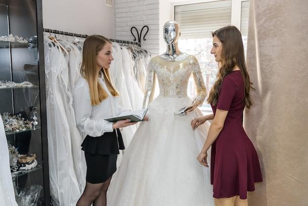 サロンのウェディング ドレスで働く若いデザイナー