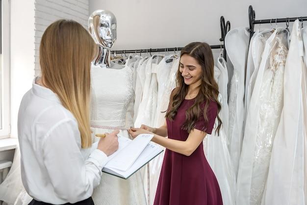 Молодые дизайнеры, работающие над свадебным платьем в салоне