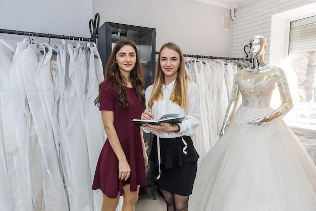 サロンでウェディングドレスで働く若いデザイナー