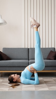 영은 집에서 운동을하는 자신감 슬림 여성을 결정했습니다. 검역 기간 동안 집에서 피트니스 트레이너 훈련. 밝고 모던 한 인테리어