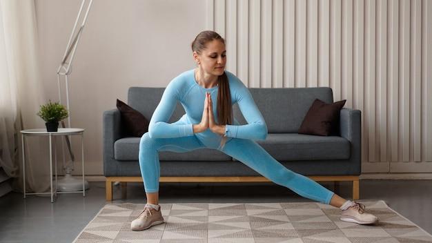若いは家で運動をしている自信を持ってスリムな女性を決定しました。フィットネストレーナーは、検疫中に自宅でトレーニングを行います。明るくモダンなインテリア