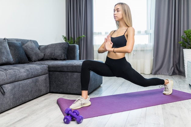Young determined confident slim woman doing exercises on the mat looking straight forward at home