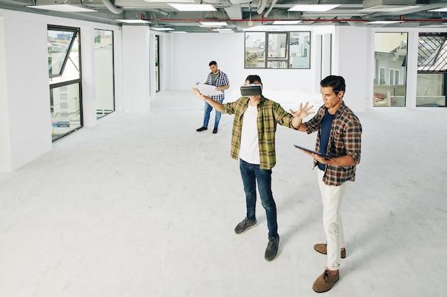 Молодые разработчики тестируют новое приложение виртуальной реальности в пустой комнате строящегося здания