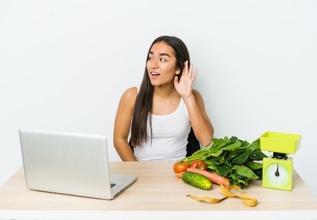 Женщина молодого диетолога азиатская изолированная на белой предпосылке пытается слушать сплетню.