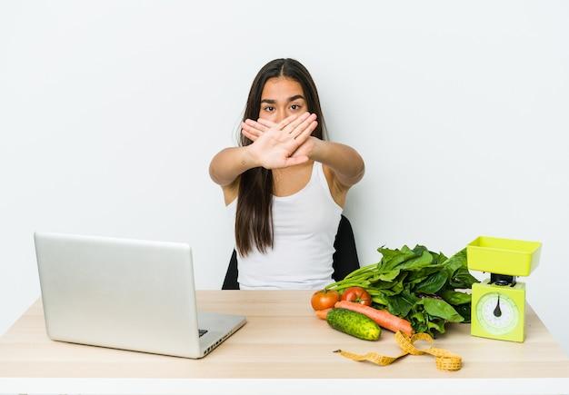Азиатская женщина молодой диетолог изолирована на белом, делая жест отрицания