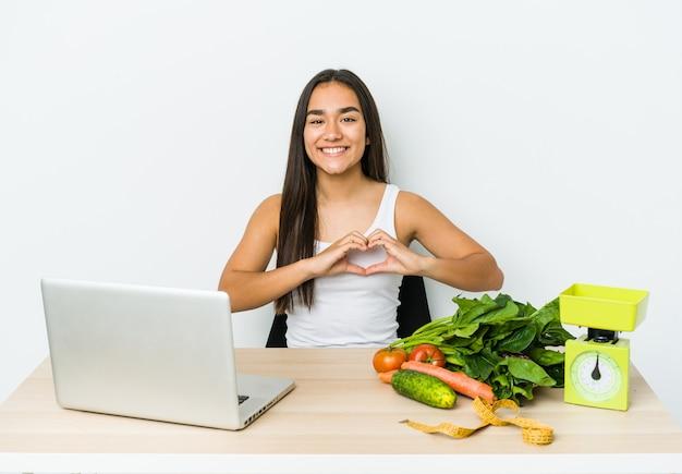 笑顔と手でハートの形を示す白い壁に分離された若い栄養士アジア人女性。